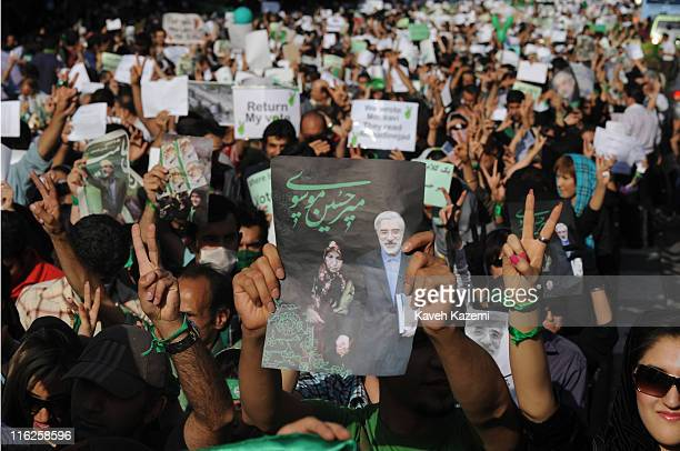 Demonstrators carry banners and pictures of Mir Hossein Mousavi the defeated reformist candidate during a march on Karimkhan Street Tehran 17th June...