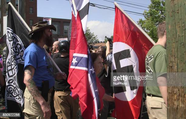 Demonstrators carry confederate and Nazi flags during the Unite the Right free speech rally at Emancipation Park in Charlottesville Virginia USA on...