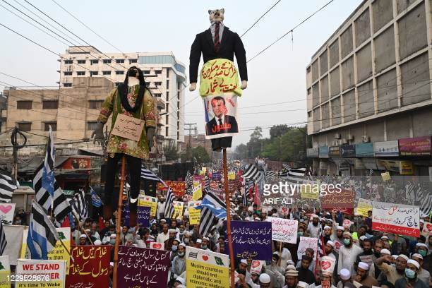 Demonstrators carry effigies of Asia Bibi , a Pakistani Christian woman who spent eight years on death row on blasphemy charges, and French President...