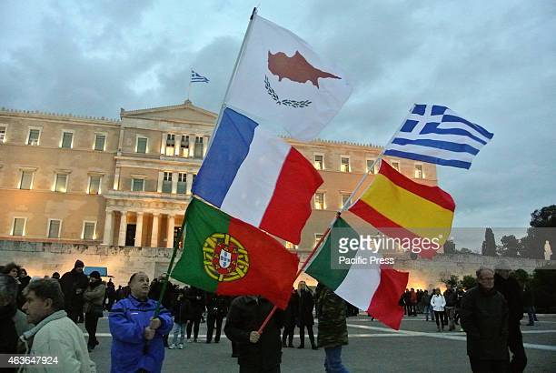 Demonstrators carry flags of Cyprus France Portugal Italy Spain and flag Greeks are on the 4th day of their rally to support the Greek government...