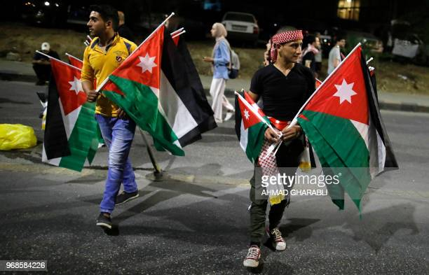 Demonstrators carry Jordanian flags during a protest near the prime minister's office in Amman Jordan on June 6 2018 Jordanian Prime Minister Hani...