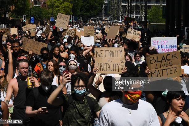 Demonstrators carry placards as they march in the road near the US Embassy in central London on May 31, 2020 to protest the death of George Floyd, an...
