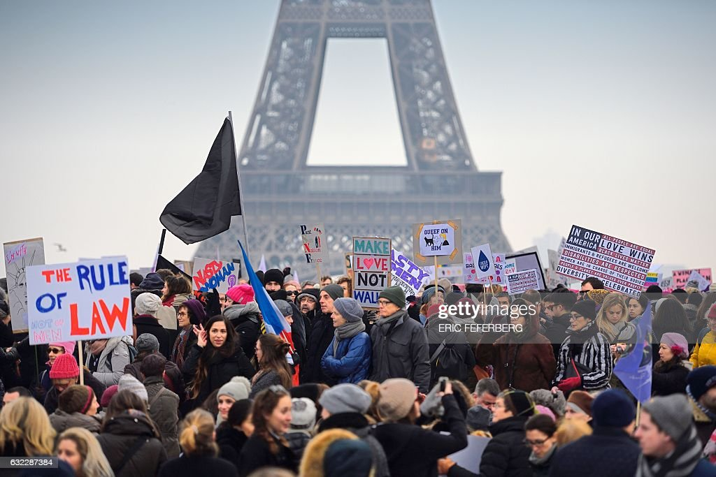 Demonstrators carry placards during a rally in solidarity with supporters of the Women's March in Washington and many other cities on January 21, 2017 at the Place de Trocadero in Paris, one day after the inauguration of the US President Donald Trump. Protest rallies were held in over 30 countries around the world in solidarity with the Washington Women's March in defense of press freedom, women's and human rights following the official inauguration of Donald J Trump as the 45th President of the United States of America. / AFP / ERIC