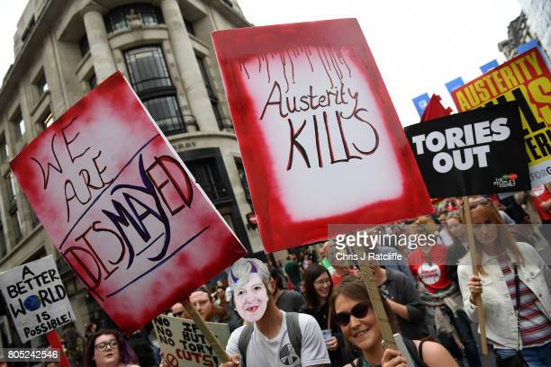 Demonstrators carry placards during the 'Not One Day More' march on Regent Street on July 1 2017 in London England Thousands of protesters joined the...