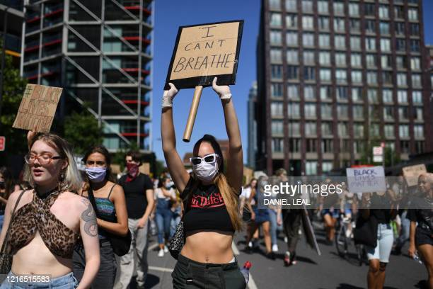 Demonstrators carry placards with slogans as they march in the road outside the US Embassy in London on May 31, 2020 to protest the death of George...