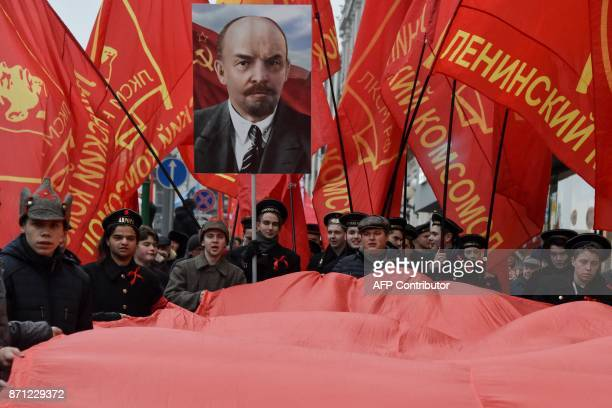 Demonstrators carry red flags and a portrait of the Soviet Union founder Vladimir Lenin as they attend a rally marking the 100th anniversary of the...