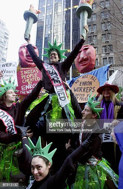 Demonstrators carry signs as they protest the World Economic Forum at Sixth Ave and 55th St
