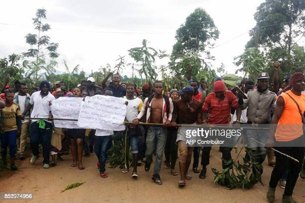 Demonstrators carry signs during a protest against perceived discrimination in favour of the country's francophone majority on September 22 2017 in...