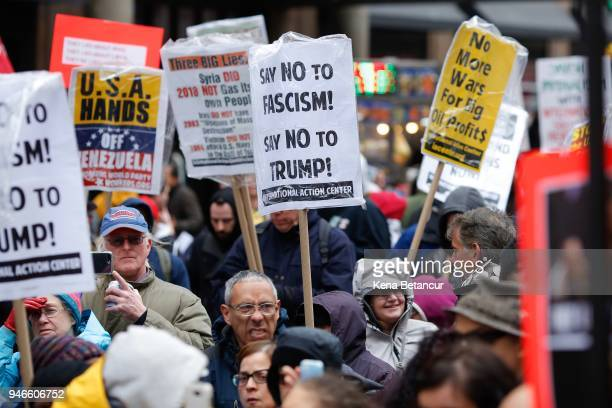 Demonstrators carry signs during an antiwar protest after President Donald Trump launched airstrikes in Syria April 15 2018 in New York City United...