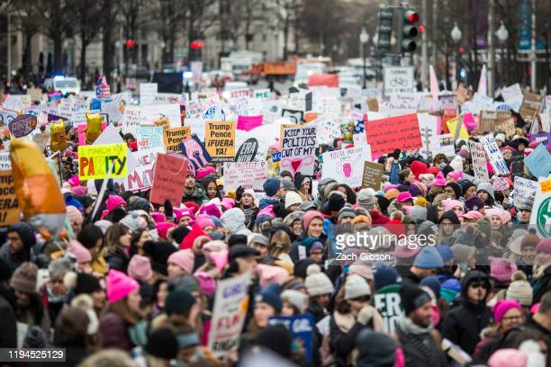 Demonstrators carry signs during the 2020 Women's March on January 18, 2020 in Washington, DC. Marches were held nationwide in cities including New...