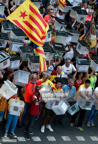 Demonstrators carry the ballot boxes used one year ago during a demonstration in Barcelona on October 1 2018 to commemorate the first anniversary of...