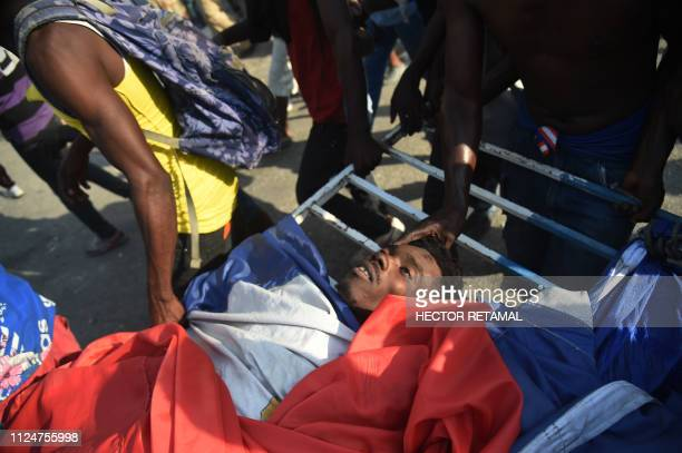 Demonstrators carry the body of a protester who died during the clashes with the police near to the National Palace in the centre of Haitian Capital...
