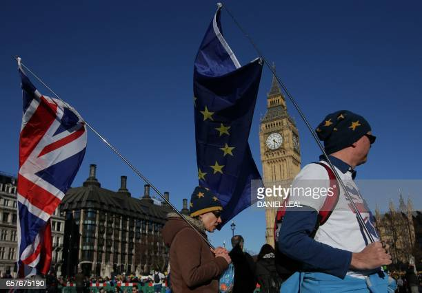 Demonstrators carry Union and EU flags as they pass the Houses of Parliament during a rally following an anti Brexit proEuropean Union march in...