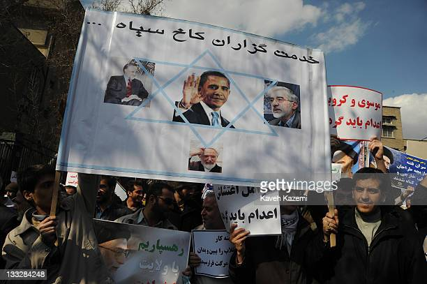 Demonstrators carrying a banner with pictures of reformist leaders, Mehdi Karroubi , Mir Hossein Mousavi and Mohammad Khatami showing them with...