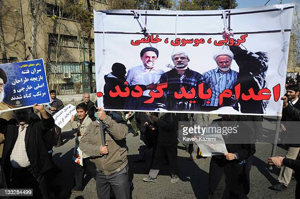 Demonstrators carrying a banner with pictures of reformist leaders Karroubi, Mousavi and Khatami showing them on the hanging rope, calling for their...