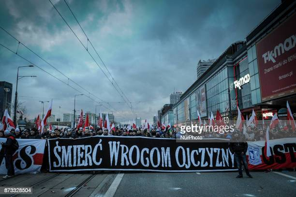 Demonstrators carrying a banner with quotDeath to Enemies of the Homelandquot await the start of a nationalist march on Independence Day on November...