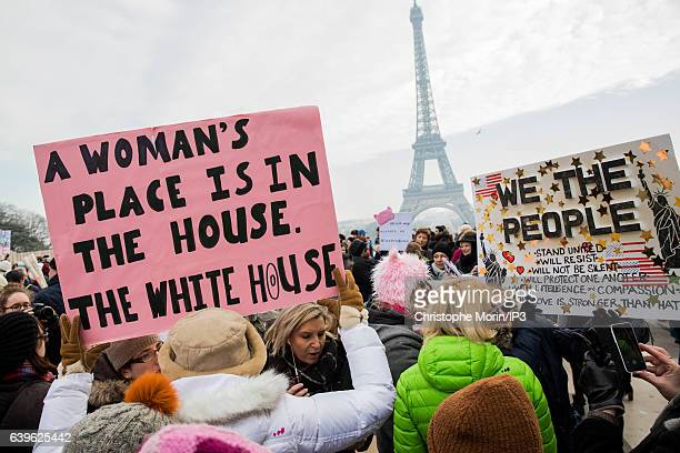 Demonstrators carrying banners and placards take part in the Women's March next to the Eiffel Tower on the Parvis des Droits de l'Homme on January 21...