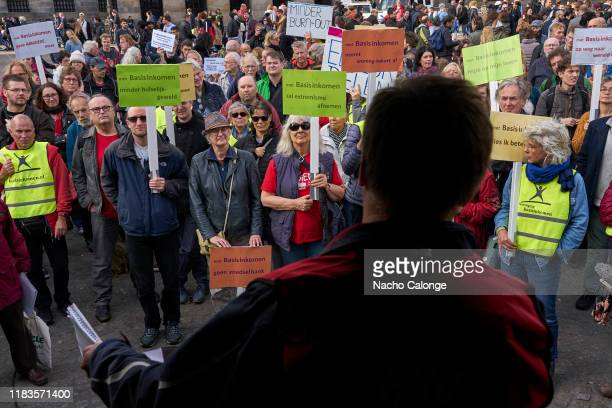 Demonstrators carrying placards listen to leaders of the demonstration for basic income on October 26 2019 in Amsterdam Netherlands The protesters...