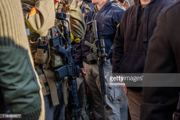 Demonstrators carrying rifles attend the Virginia Citizens Defense League Lobby Day rally at the state capitol in Richmond Virginia US on Monday Jan...