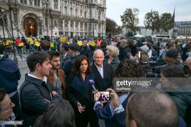 Demonstrators carrying yellow signs to demand better housing conditions in Paris geather behind the Mayor of Paris Anne Hidalgo as she speaks with...