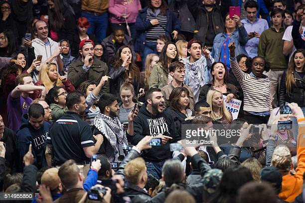 Demonstrators celebrate after learning a rally for Republican presidential candidate Donald Trump at the University of Illinois at Chicago would be...