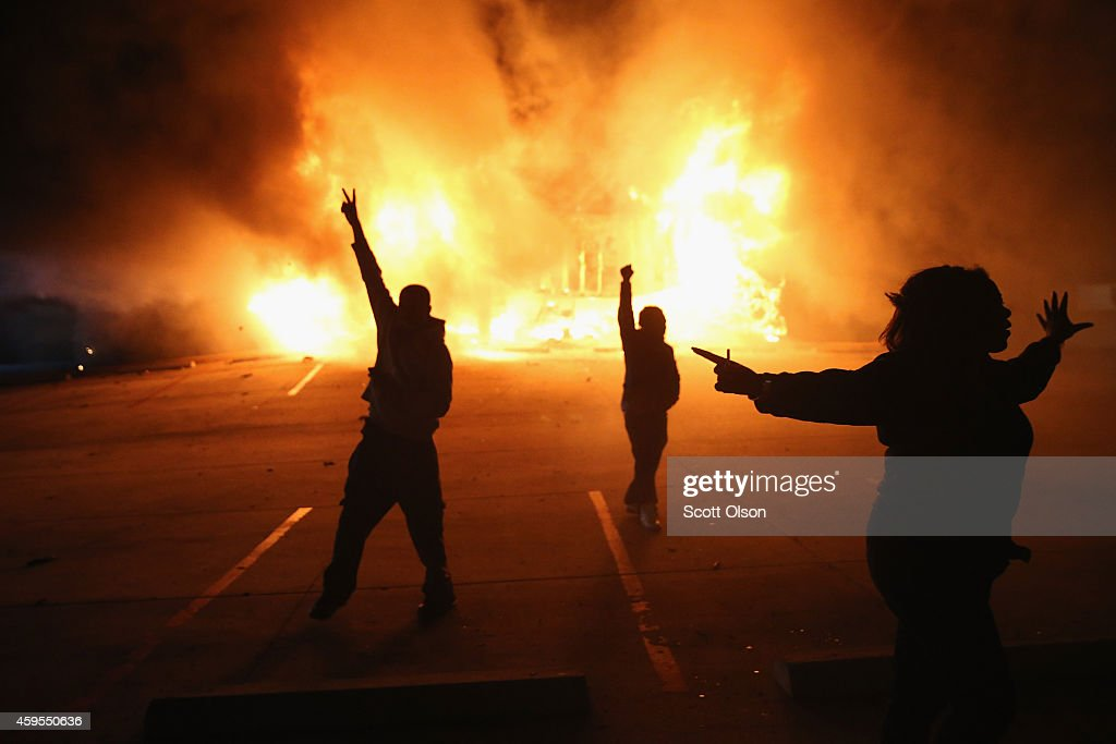 Demonstrators celebrate as a business burns after it was set on fire during rioting following the grand jury announcement in the Michael Brown case on November 24, 2014 in Ferguson, Missouri. Ferguson has been struggling to return to normal after Brown, an 18-year-old black man, was killed by Darren Wilson, a white Ferguson police officer, on August 9. His death has sparked months of sometimes violent protests in Ferguson. A grand jury today declined to indict officer Wilson.