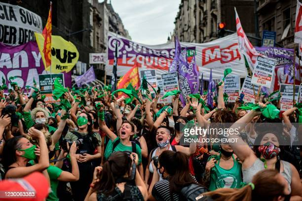 Demonstrators celebrate with green headscarves - the symbol of abortion rights activists - outside the Argentine Congress in Buenos Aires on December...
