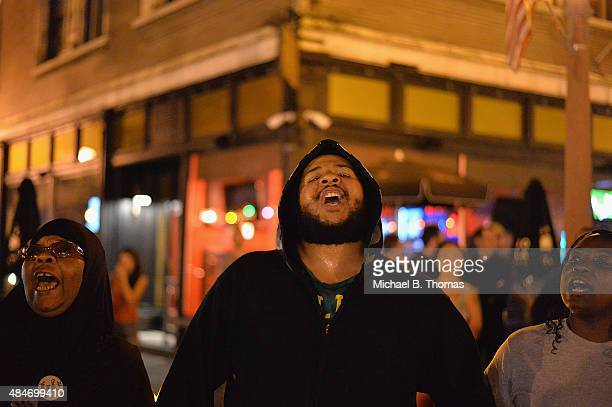 Demonstrators chant aloud during a protest action through the Central West End of St Louis Missouri on August 20 2015 After a night of unrest sparked...