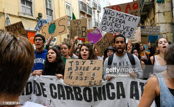 Demonstrators chant and hoist placards at a rally in support of the climate strike on November 29, 2019 in Lisbon, Portugal. The rally, part of the...