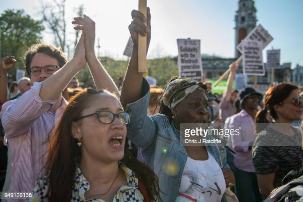 Demonstrators chant and hold placards during a protest in support of the Windrush generation in Windrush Square Brixton on April 20 2018 in London...