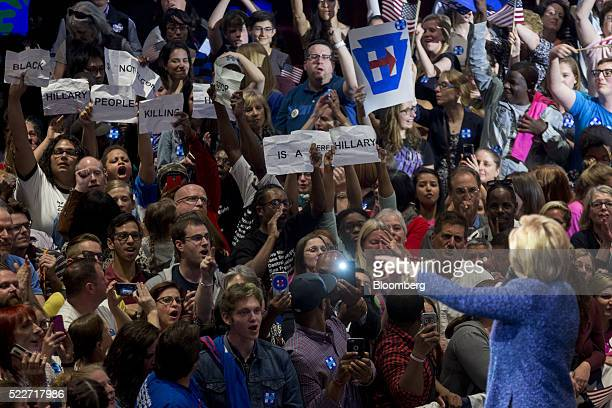 Demonstrators chant and hold up pieces of paper as Hillary Clinton former Secretary of State and 2016 Democratic presidential candidate right speaks...