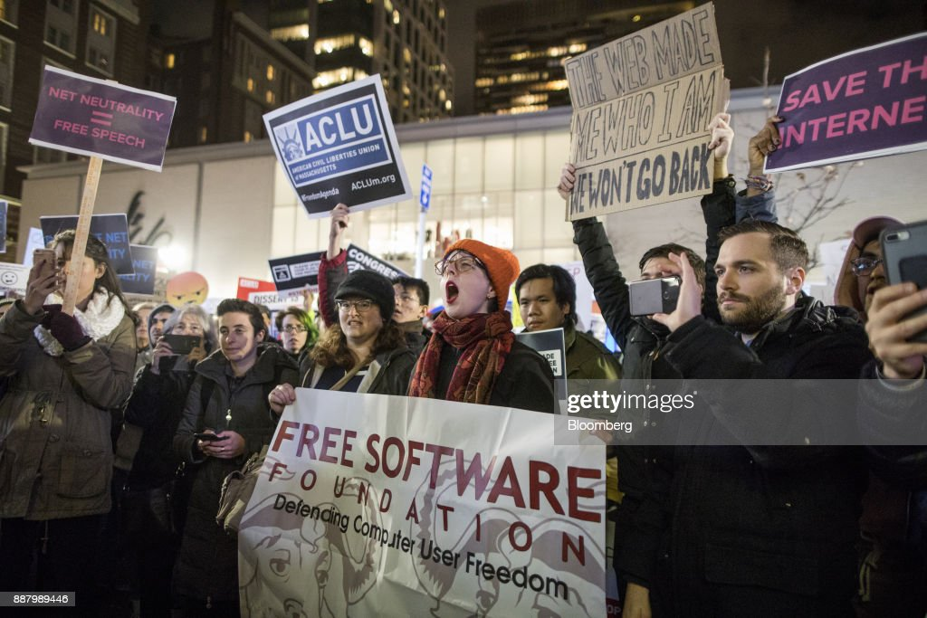 Demonstrators chant and hold up signs during a net neutrality protest outside a Verizon Communications Inc. store in Boston, Massachusetts, U.S., on Thursday, Dec. 7, 2017. The debate over internet regulation has steadily morphed over the last few years from an insular fight between telecom experts into a standard-issue political screaming match. Photographer: Scott Eisen/Bloomberg via Getty Images