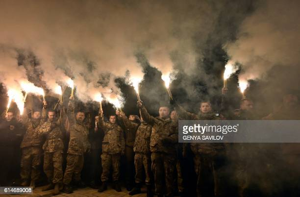 """Demonstrators chant slogans and raise flares during a rally in Kiev on October 14, 2016. - Few thousands members of """"Azov"""" civil corps and veterans..."""