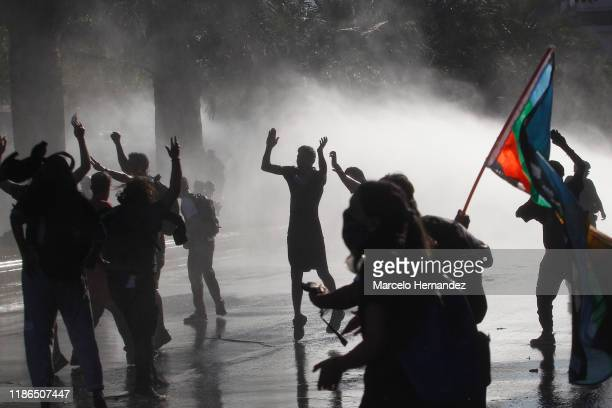 Demonstrators chant slogans as they are fired water by the riot police during protests against president Piñera at Plaza Italia on December 4, 2019...