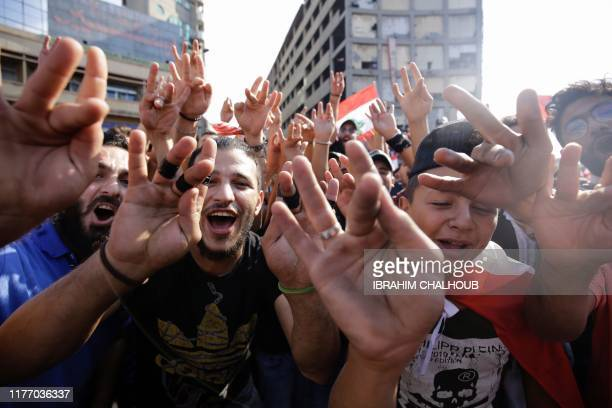 Demonstrators chant slogans as they display their middle fingers during a protest against dire economic conditions in the central Nur square in the...