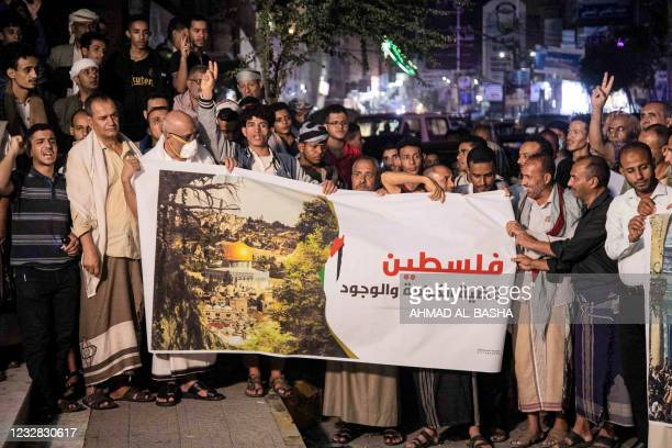 Demonstrators chant slogans as they gather in a vigil in solidarity with the Palestinian people in Yemen's third city of Taez late on May 11, 2021. -...