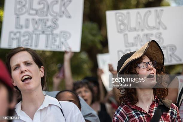 Demonstrators cheer for a speaker during a rally at Marshall Park September 24 2016 in uptown Charlotte North Carolina Protests have disrupted the...