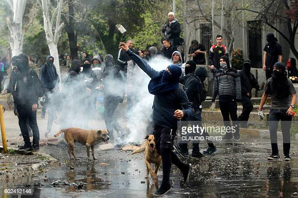Demonstrators clash with police as human rights activists march in Santiago on September 11 2016 commemorating the 43rd anniversary of the military...