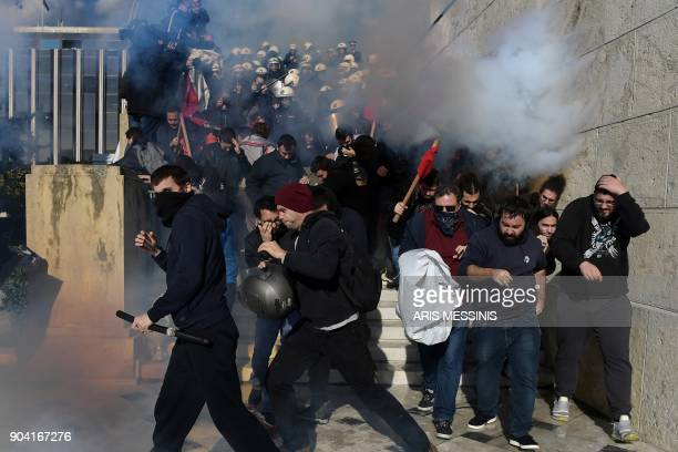 TOPSHOT Demonstrators clash with police as they try to take the stairs leading to the parliament building in Athens on January 12 as part of a strike...