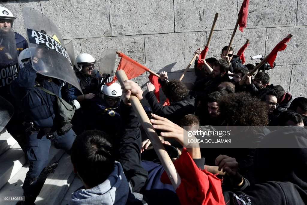 Demonstrators clash with police as they try to take the stairs leading to the parliament building in Athens on January 12, 2018, as part of a strike wave against changes to a 36-year-old industrial action law demanded by the country's creditors. /