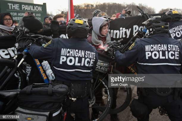 Demonstrators clash with police before the start of a speech by white nationalist Richard Spencer who popularized the term 'altright' at Michigan...