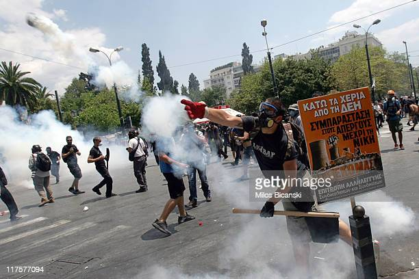 Demonstrators clash with police through the tear gas during a protest against plans for new austerity measures on June 28 2011 in Athens Greece...