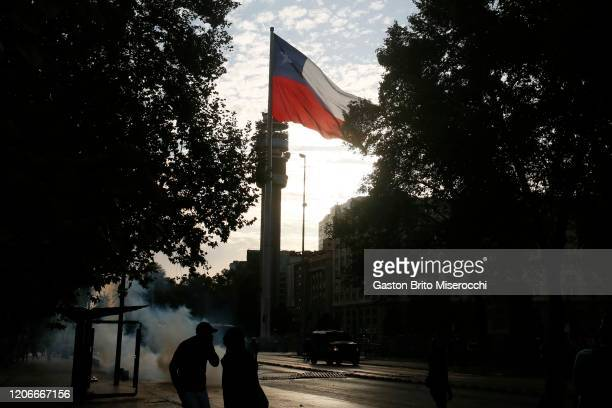 Demonstrators clash with riot police as the flag of Chile waves during protests against the government of Sebastián Piñera on its second anniversary...