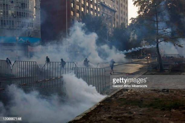Demonstrators clash with riot police at Alameda Avenue during protests against the government of Sebastián Piñera on its second anniversary on March...