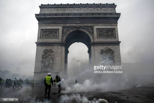 Demonstrators clash with riot police at the Arc de Triomphe during a protest of Yellow vests against rising oil prices and living costs, on December...
