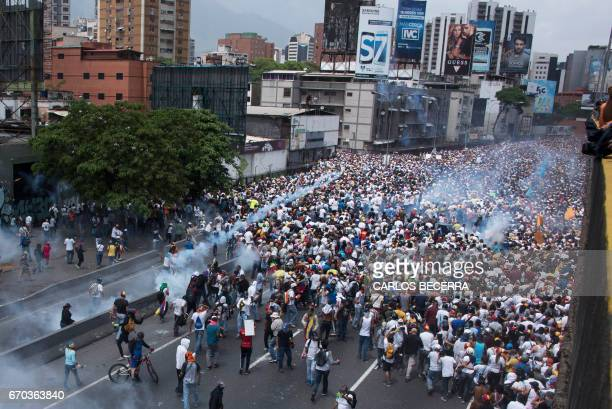 TOPSHOT Demonstrators clash with riot police during a march against Venezuelan President Nicolas Maduro in Caracas on April 19 2017 Venezuelans took...