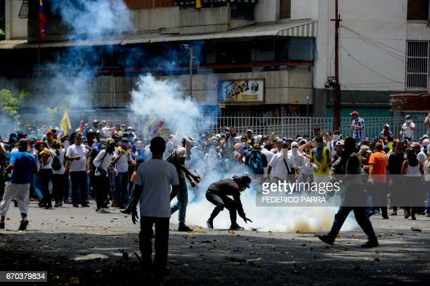 Demonstrators clash with riot police during a march against Venezuelan President Nicolas Maduro in Caracas on April 19 2017 Venezuelans took to the...