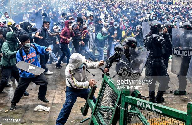 Demonstrators clash with riot police during a protest against a tax reform bill launched by Colombian President Ivan Duque, in Bogota, on April 28,...
