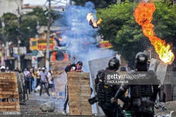 Demonstrators clash with riot police during a protest against a tax reform bill launched by Colombian President Ivan Duque, in Cali, Colombia on...