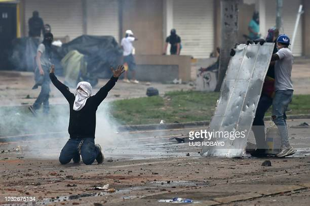 Demonstrators clash with riot police during a protest against a tax reform bill launched by President Ivan Duque, despite the president then ordered...